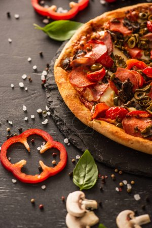 Photo for Selective focus of delicious Italian pizza with salami near vegetables on black background - Royalty Free Image