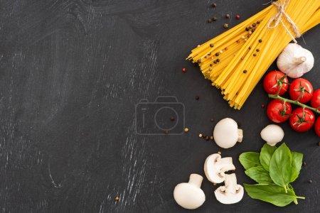 Photo pour Vue du dessus des spaghettis italiens crus aux légumes et aux épices sur fond noir - image libre de droit