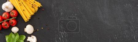 Photo pour Vue du dessus des spaghettis italiens crus avec des légumes et des épices sur fond noir, panoramique - image libre de droit