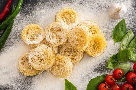 von oben auf rohe Capellini-Pasta mit Gemüse und Mehl