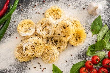 Photo pour Vue du dessus des pâtes crues Capellini aux légumes, épices et farine - image libre de droit