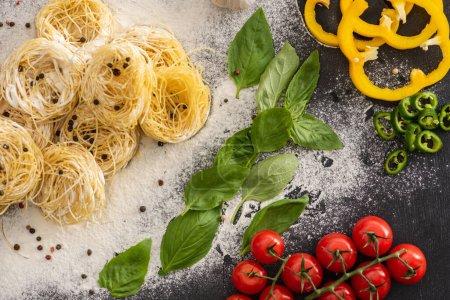 von oben auf rohe Capellini mit Gemüse, Gewürzen und Mehl