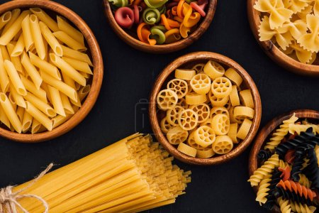 Photo for Top view of assorted colorful Italian pasta in wooden bowls on black background - Royalty Free Image