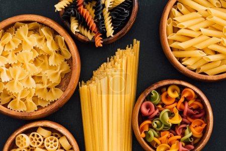 Photo pour Vue du dessus de pâtes italiennes colorées assorties dans des bols en bois sur fond noir - image libre de droit