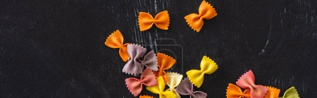 Photo for Top view of colorful raw farfalle pasta on black wooden background, panoramic shot - Royalty Free Image