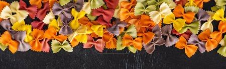 Photo pour Vue de dessus de pâtes farfalle crues colorées sur fond de bois noir, panoramique - image libre de droit