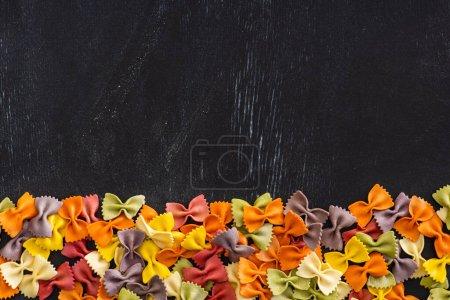 Photo pour Vue de dessus des pâtes farfalle crues colorées sur fond en bois noir - image libre de droit