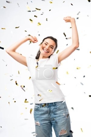 Photo for Excited woman in white t-shirt with hands above head near confetti on white - Royalty Free Image