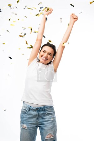 Photo for Excited young woman in white t-shirt with hands above head near confetti on white - Royalty Free Image