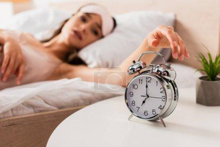 selective focus of woman touching retro alarm clock