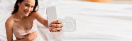 Photo pour Plan panoramique de jeune femme enceinte prenant selfie dans la chambre - image libre de droit