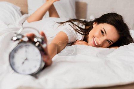 Photo pour Foyer sélectif de la jeune femme couchée sur le lit et atteignant rétro réveil - image libre de droit