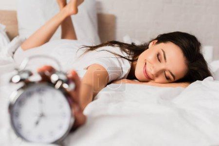 Photo pour Foyer sélectif de la femme avec les yeux fermés couché sur le lit et atteignant rétro réveil - image libre de droit