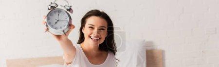 Photo pour Récolte horizontale de jeune femme tenant rétro réveil - image libre de droit