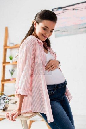 Photo pour Femme enceinte touchant le ventre et debout près de la table avec réveil vintage - image libre de droit