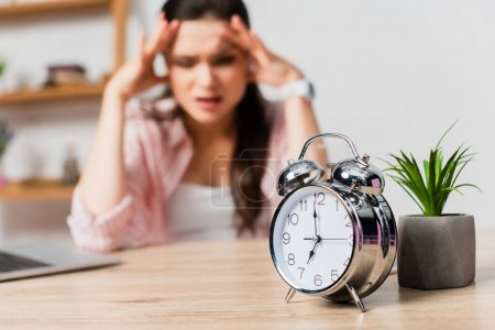 selective focus of vintage alarm clock near plant and stressed woman touching head