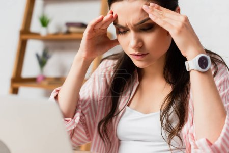selective focus of stressed woman with closed eyes touching head at home