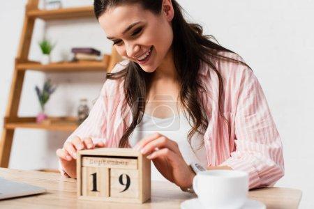 Photo pour Foyer sélectif de la femme brune touchant cubes en bois avec date près de tasse - image libre de droit
