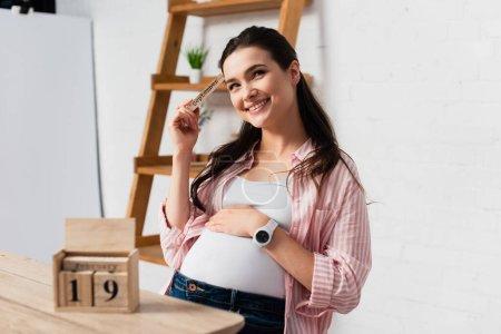 Photo pour Foyer sélectif de la femme enceinte toucher le ventre près de cubes en bois avec la date - image libre de droit
