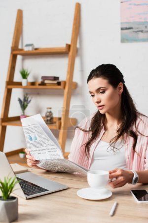 selective focus of pregnant woman reading newspaper and holding cup near gadgets