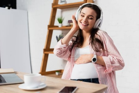 Photo pour Foyer sélectif de la femme enceinte avec les yeux fermés écouter de la musique dans les écouteurs sans fil près de gadgets et tasse - image libre de droit