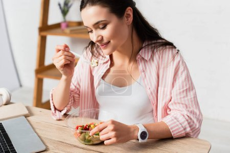 young brunette woman holding plastic fork with fresh salad near takeaway container
