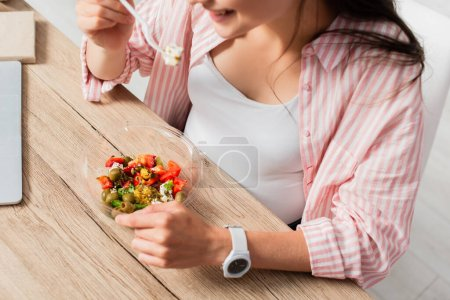 cropped view of pregnant woman holding plastic fork near takeaway container with fresh salad