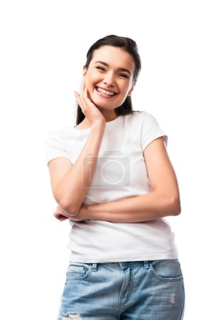 young brunette woman in white t-shirt touching face and looking at camera isolated on white
