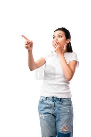 schockierte junge Frau in weißem T-Shirt zeigt mit dem Finger und bedeckt Mund isoliert auf weiß