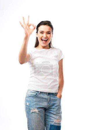 junge Frau in weißem T-Shirt und Jeans steht mit der Hand in der Tasche und zeigt O.K. Zeichen isoliert auf weiß