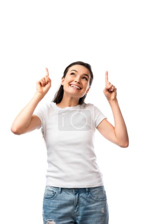 brunette woman in white t-shirt pointing with fingers and looking up isolated on white