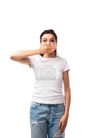 mujer conmocionada en camiseta blanca y jeans que cubren la boca aislada en blanco