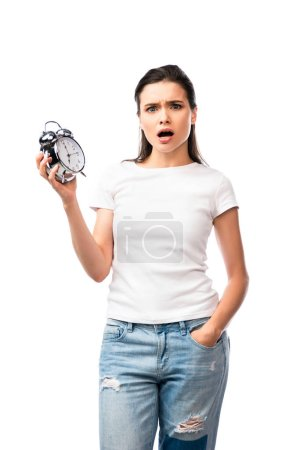 shocked woman in white t-shirt and jeans standing with hand in pocket and holding retro alarm clock isolated on white