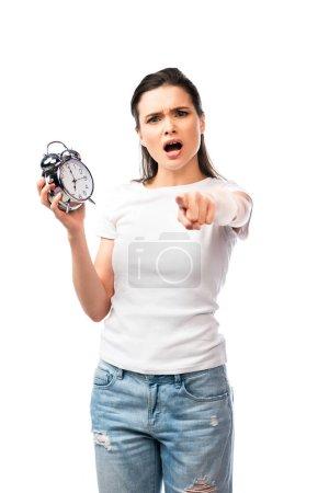 foyer sélectif de la femme en t-shirt blanc et jeans tenant rétro réveil tout en pointant avec doigt isolé sur blanc