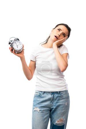 femme brune fatiguée en t-shirt blanc et jeans tenant rétro réveil isolé sur blanc