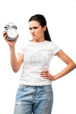 Photo pour Femme mécontente en t-shirt blanc tenant rétro réveil tandis que debout avec la main sur la hanche isolé sur blanc - image libre de droit