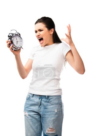 angry woman in white t-shirt holding retro alarm clock while screaming and gesturing isolated on white