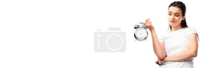 panoramic concept of dissatisfied woman in white t-shirt looking at retro alarm clock isolated on white