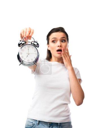 Photo pour Foyer sélectif de femme choquée en t-shirt blanc regardant rétro réveil isolé sur blanc - image libre de droit
