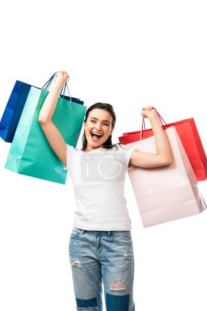 brunette woman with open mouth holding shopping bags isolated on white