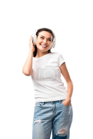 young woman in white t-shirt and wireless headphones standing with hand in pocket isolated on white