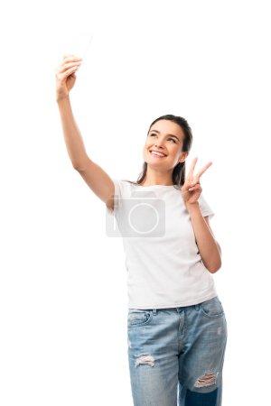 Photo pour Femme brune en t-shirt blanc prenant selfie et montrant signe de paix isolé sur blanc - image libre de droit