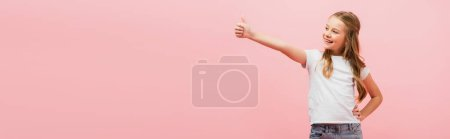 Photo pour Image horizontale de la fille en t-shirt blanc avec la main sur la hanche montrant pouce vers le haut tout en regardant loin isolé sur rose - image libre de droit