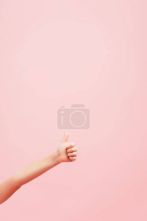 partial view of kid showing thumb up isolated on pink with copy space