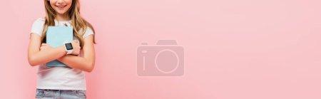 Photo pour Vue recadrée de fille dans smartwatch tenant livre tout en se tenant isolé sur rose, image horizontale - image libre de droit