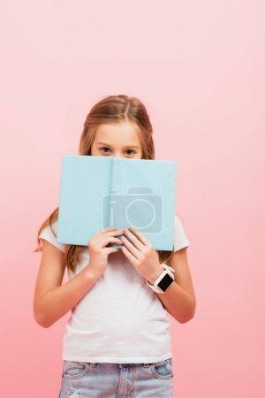 Photo pour Fille dans smartwatch obscurcissement visage avec livre tout en regardant caméra isolé sur rose - image libre de droit