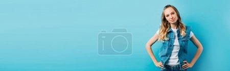 Photo pour Récolte panoramique de jeune femme en gilet en denim debout avec les mains sur les hanches isolées sur bleu - image libre de droit