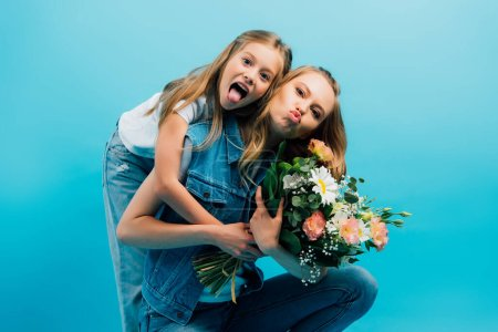 Photo for Girl sticking out tongue and hugging mother pouting lips while holding bouquet of flowers isolated on blue - Royalty Free Image