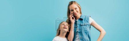 Photo pour Plan panoramique de jeune femme en gilet en denim parlant sur smartphone près de curieuse fille isolée sur bleu - image libre de droit