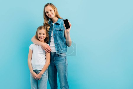 Photo for Young woman in denim clothes showing smartphone with blank screen while hugging child in white t-shirt and jeans isolated on blue - Royalty Free Image